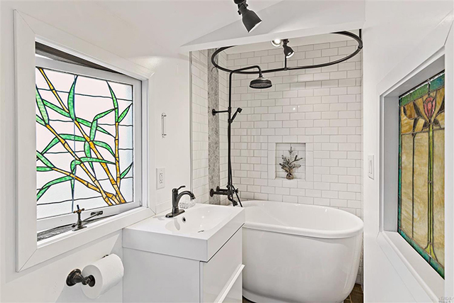 The bathroom features colorful stained glass.