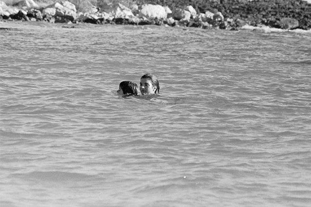 The original caption: Mrs. John F. Kennedy and her son, John Jr., enjoy a swim in Antiqua waters December 27, at the start of a two-week vacation.